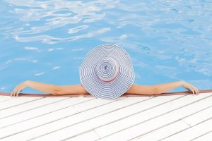 Woman lounging in a pool wearing a sun hat.