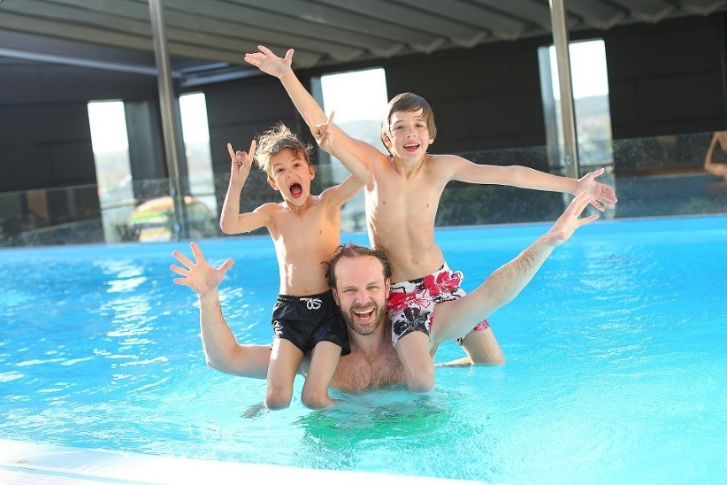 A Dad with two kids on his shoulders playing in the pool.